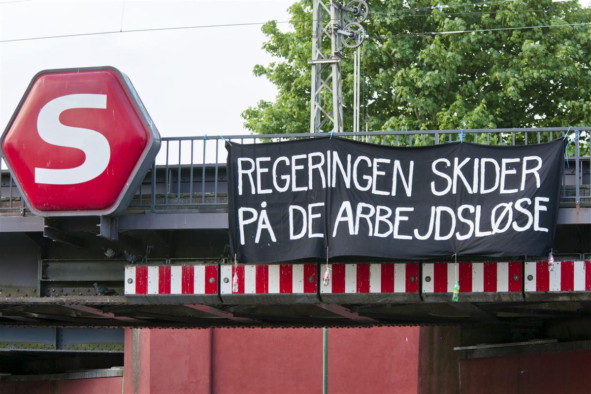 Ordvalget i a-kasserne er mere raffineret end demonstranternes på dette banner. Men meningen er ikke til at tage fejl af: Der er sparet nok på de arbejdsløse, mener AK-Samvirke.